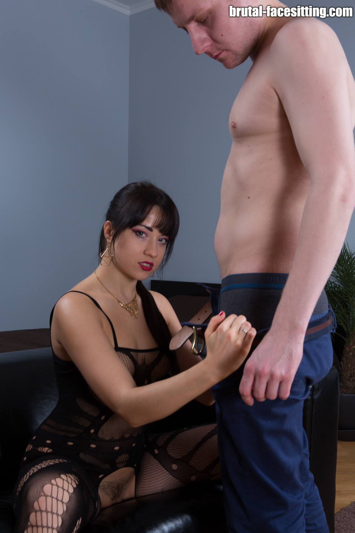 Black-haired dominant woman undressing pants from slave